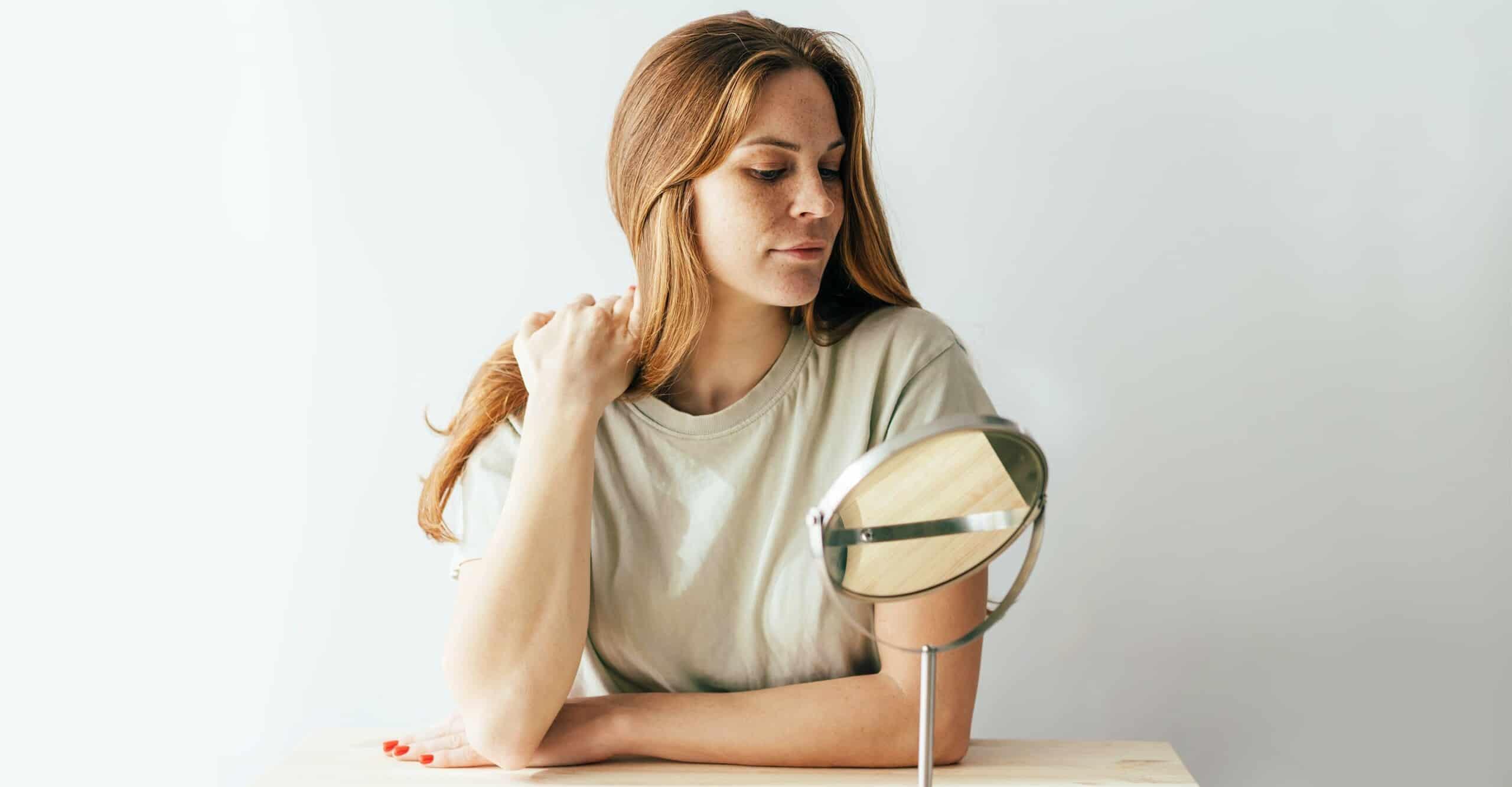 woman looking at hair in small desktop mirror