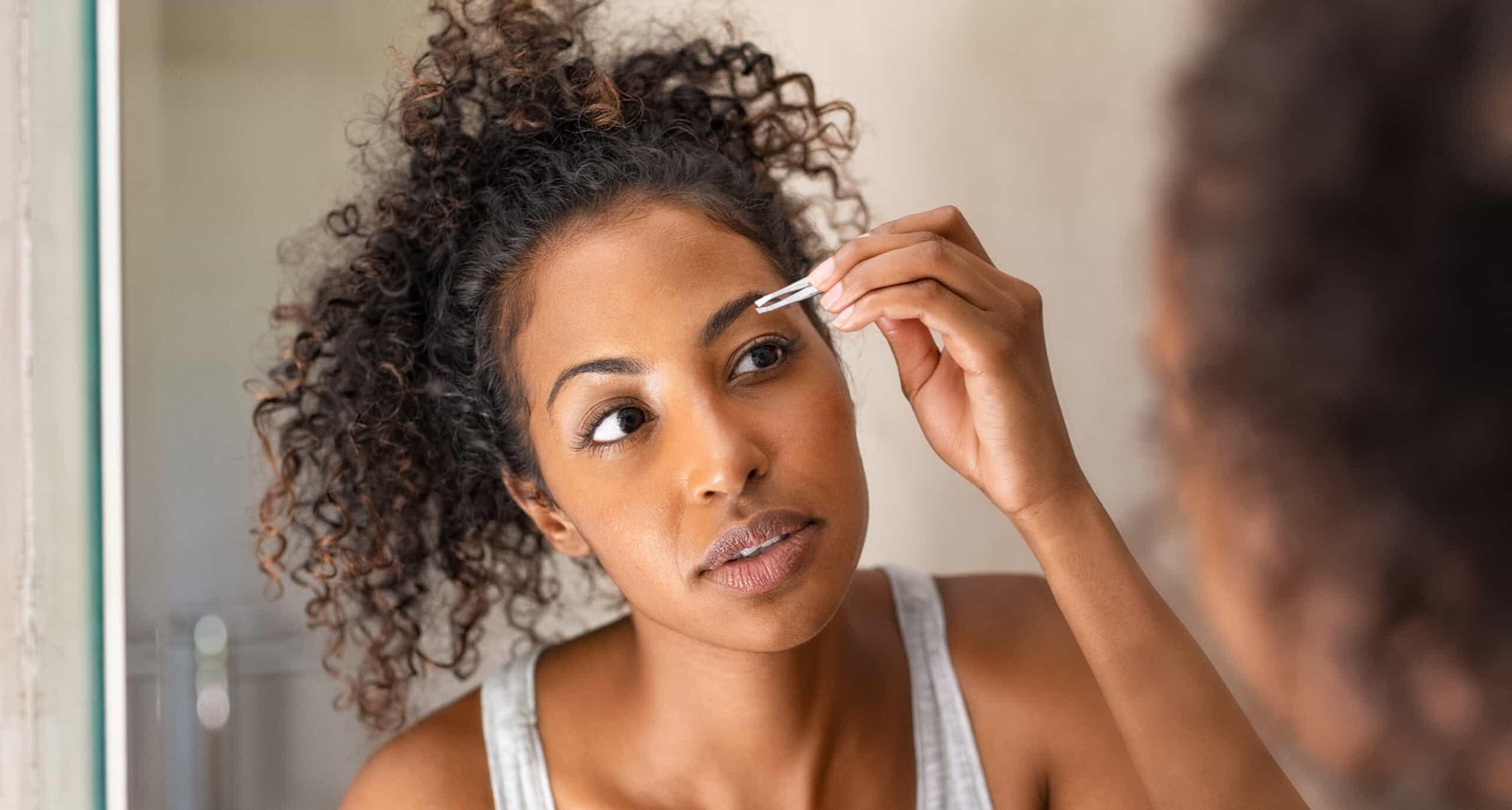 woman shaping eyebrows at home